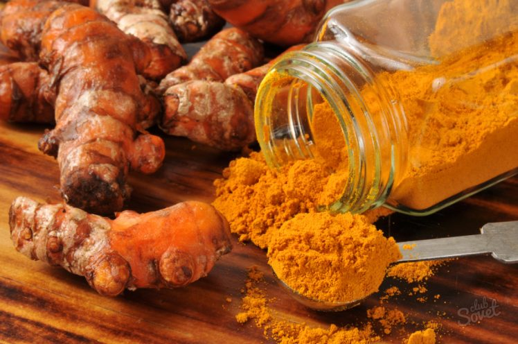Fresh turmeric root, and ground spice - shallow depth of field